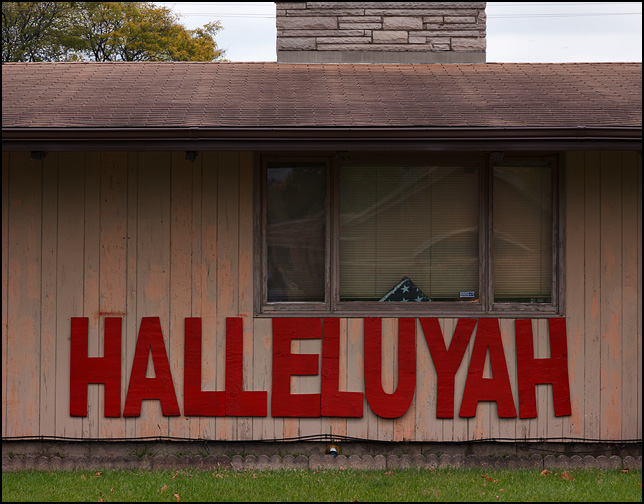 The word Hallelujah, spelled as Halleluyah, written out in giant red plywood letters mounted on the front of a ranch-style house on Benham Avenue in Elkhart, Indiana. A folded American flag is displayed in the front window.