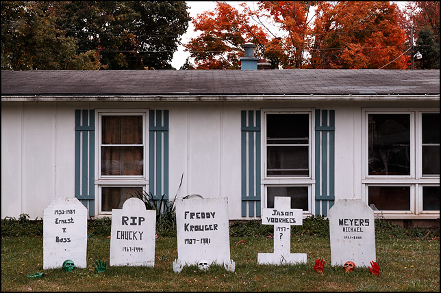 A house decorated for Halloween with plywood tombstones in the yard with the names of horror movie killers Michael Myers, Jason Voorhees, and Freddie Krueger. Skeletons are crawling out of the ground in front of the gravestones.