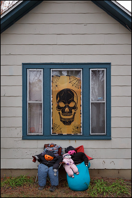 Halloween decorations on an old house on West Main Street in Fort Wayne, Indiana. An orange window covering has a large skull and spider webs. People with jack-o-lantern heads sit on chairs under the window in front of the house.