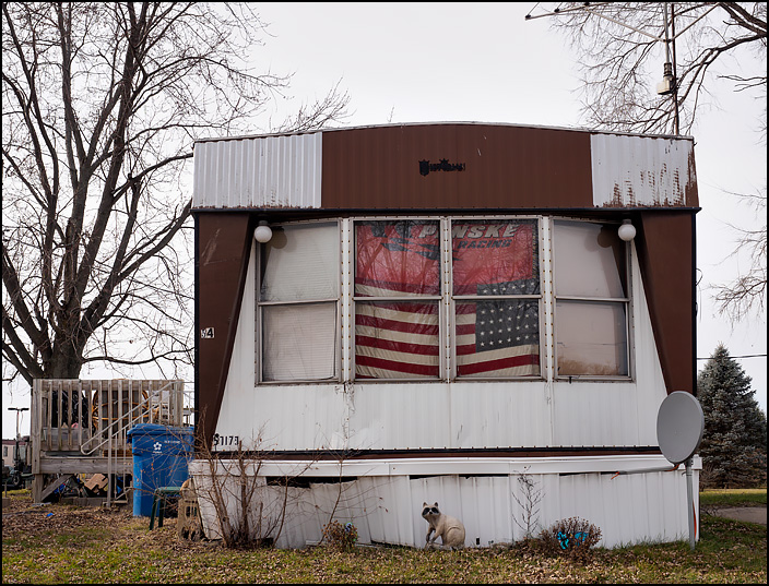 A mobile home with an American flag and a Penske Racing banner in the window. Located in a trailer park in the small town of Hamlet, Indiana.