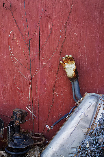 An old leather work glove stuck on an automobile gas tank leaning against a red barn.