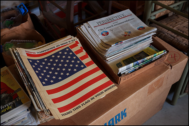 American flags printed on newsprint in the Fort Wayne newspapers, stacked up in a pile of old papers in a basement.