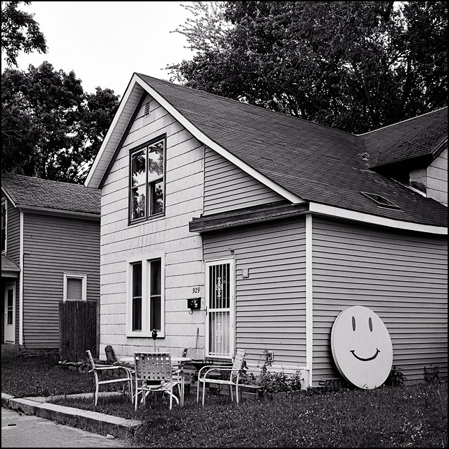 A round table painted like a smiley face leans against the side of an old house on Dewald Street in Fort Wayne, Indiana.