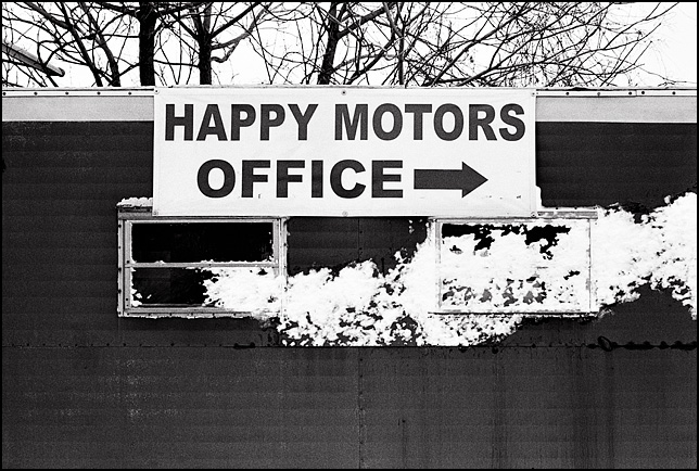 Snow covers the windows on an old office trailer with an arrow sign for the Happy Motors used car lot in Fort Wayne, Indiana.