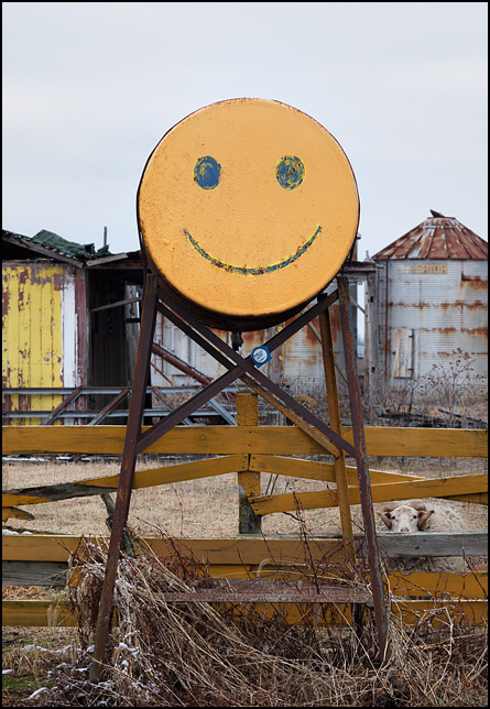 A fuel tank with a yellow happy face painted on the front of it stands in front of a barnyard fence in rural Delaware County, Indiana. A sheep looks out through the fence.