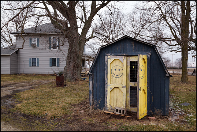 A blue barn with yellow happy faces painted on the doors stands in front of a farmhouse in rural Delaware County, Indiana.