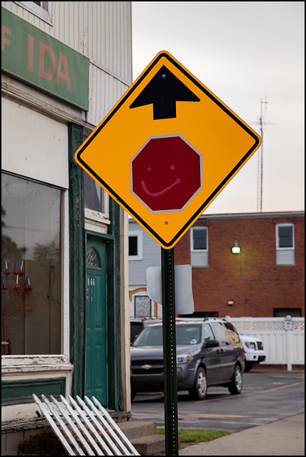 A stop-ahead road sign with a happy face painted on it in the small town of Ida, Michigan.