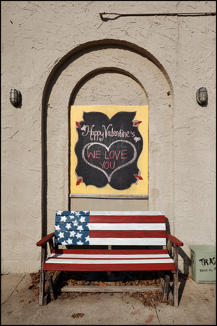 Happy Valentines - We Love You. A sign written on a chalkboard with a big heart drawn on it. The sign hangs above a bench painted like the American flag next to Little Shop of Lauras on Broadway in Fort Wayne, Indiana.