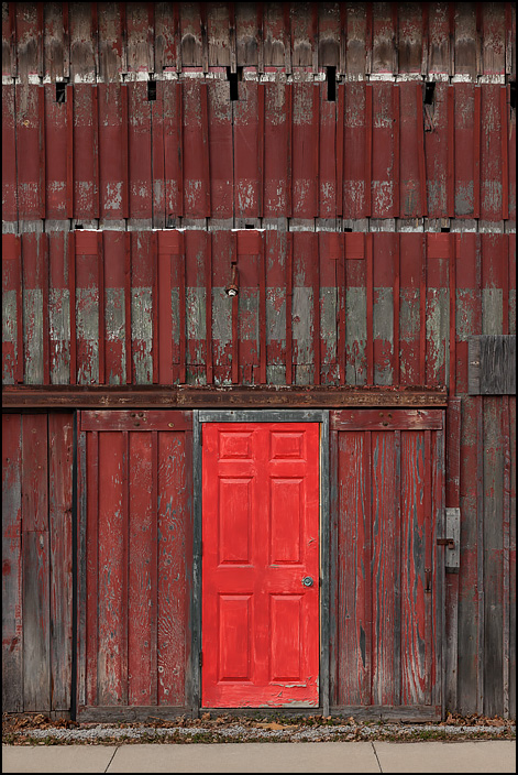 A red steel house door looks out of place on the side of an old weathered wood barn on Antwerp Road in the small town of Harlan, Indiana.