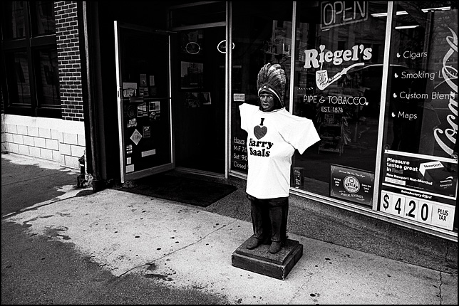 A cigar store Indian statue in front of Riegel's Pipe and Tobacco Shop in Fort Wayne wearing a t-shirt that says I Love Harry Baals.