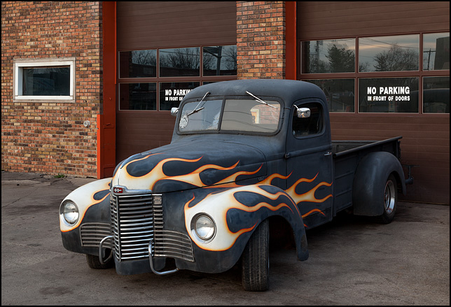 An International KB-1 pickup truck with hot-rod flames painted on the front of it sits in front of the garage doors at B&G Auto Repair in the Waynedale area of Fort Wayne, Indiana.