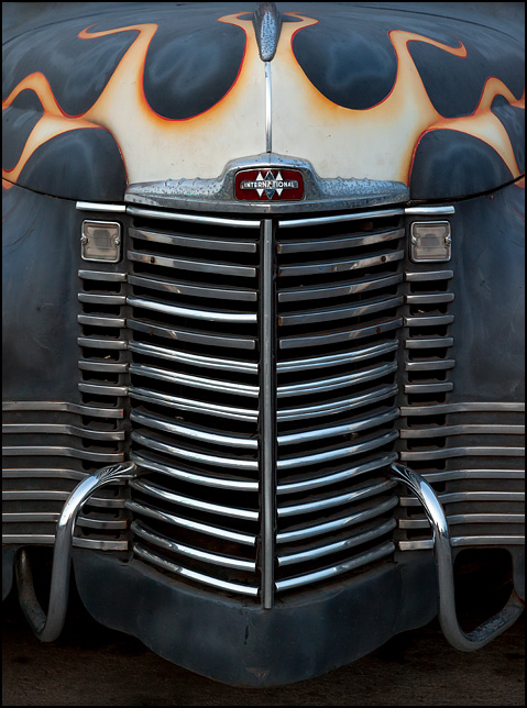 The grille of a gray International KB-1 pickup truck with hot-rod flames painted on the front and hood.