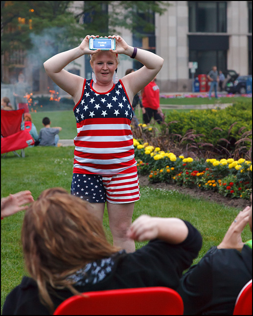 A young woman wearing an American flag tank top and shorts plays the Heads Up! smartphone game with her friends before the fireworks began on the Fourth of July in downtown Fort Wayne, Indiana.
