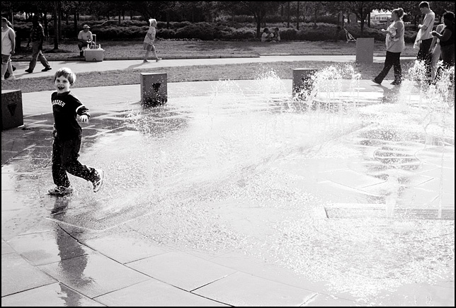 My seven year old son running through the water at the Headwaters Park fountain in Fort Wayne, Indiana.
