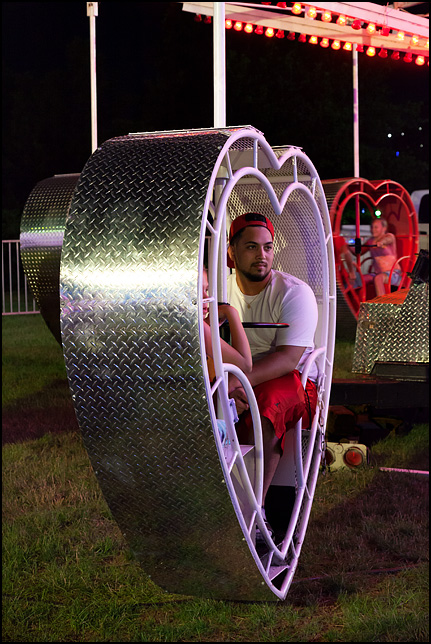 A young Hispanic man looks out from the heart-shaped pod on the Heart Flip Ride at the 2017 Three Rivers Festival in Fort Wayne, Indiana.