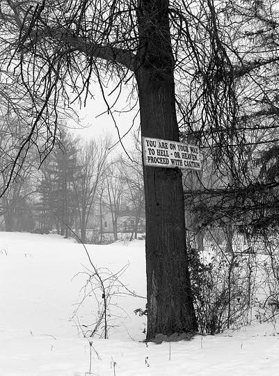 An old religious sign nailed to a tree across from Portage Middle School on Taylor Street in Fort Wayne that says You are on your way to Hell or Heaven proceed with caution. Photographed on a foggy day in winter with snow on the ground.