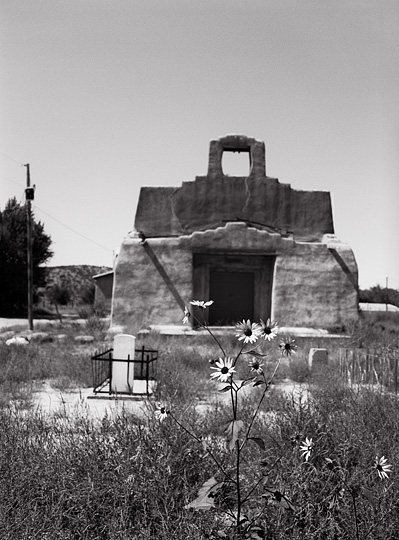Daisies grow in front of the old church and cemetery in Hernandez, New Mexico. The old adobe church is missing its bell and is surrounded by overgrown weeds.