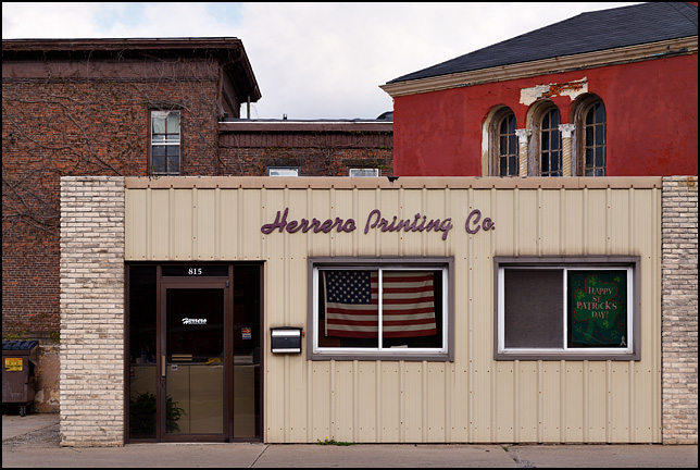 An American flag and a Happy Saint Patricks Day sign in the window of the Herrero Printing Company in Fort Wayne, Indiana.