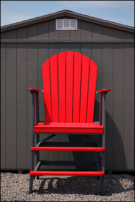 A Giant Ten Foot Tall Red Patio Chair Beside A Wooden Storage Shed At An  Outdoor