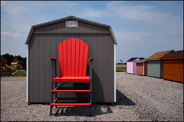 A giant ten foot tall red patio chair and several small storage sheds at an outdoor furniture store.