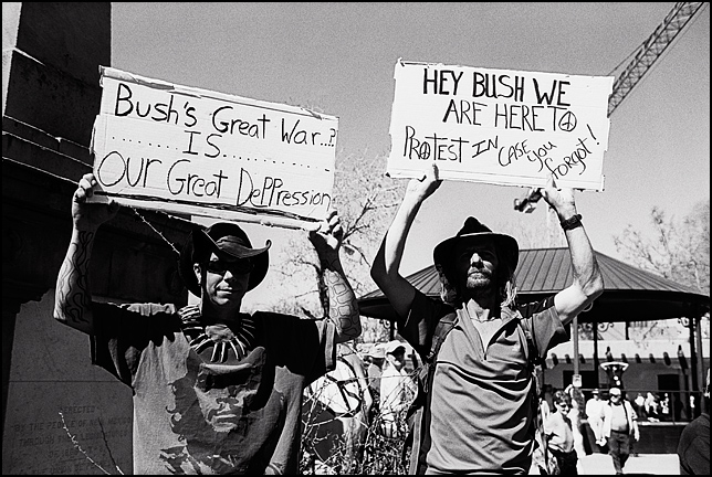 "Two young men hold protest signs during a peace demonstration on the Santa Fe Plaza. One of them holds a sign that says ""Hey Bush we're here to protest in case you forgot!"" and the other man's sign says ""Bush's great war is our great depression."" One of the protestors wears a Che Guevara t-shirt."