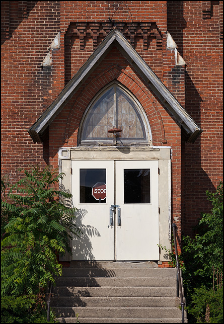 Abandoned brick church with a stop sign visible through the window on the front door. The church is on the corner of Maple Street and Smith Street in the small town of Hicksville, Ohio.