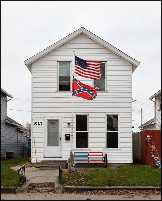 A house with both an American flag and a Confederate flag flying from a pole in the yard. A glider swing in front of the house is painted like the American flag and there is another American flag on the front door. High Street in Fort Wayne, Indiana.