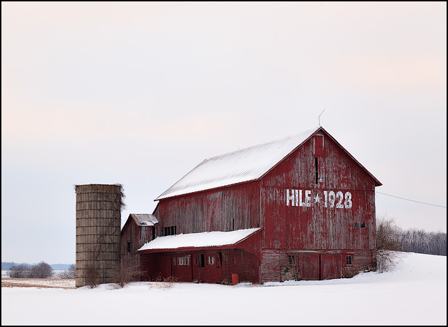 An old red barn on a snow-covered hill on US-33 in rural Noble County, Indiana. The end of the barn has HILE 1928 painted on it. Photographed near sunset on a December evening.