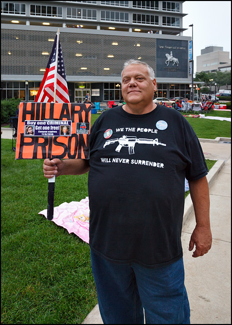 A protester holding a Hillary For Prison sign in the crowd before the 2016 Fourth of July fireworks on the Courthouse Green in downtown Fort Wayne, Indiana. A sticker on the sign has pictures of Bill and Hillary Clinton with the caption, Buy One Criminal And Get One Free. His shirt has an AR15 rifle and it says, We The People Will Never Surrender.