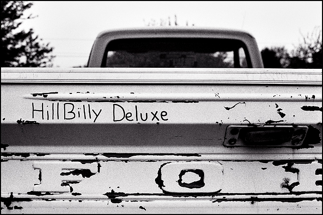 An old rusty Ford pickup truck with the phrase Hillbilly Deluxe written on the tailgate in black marker ink.