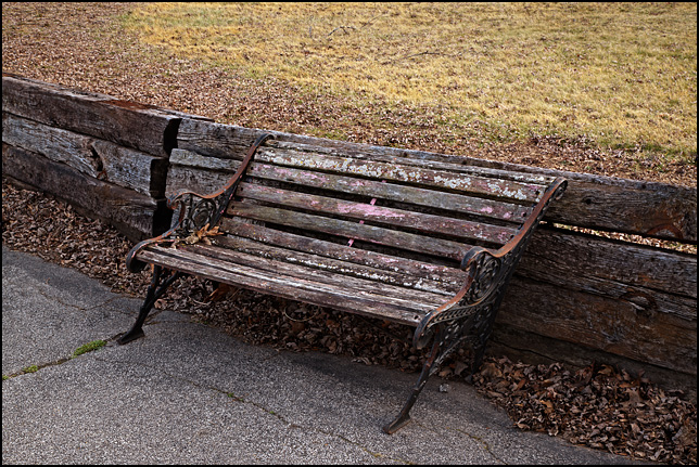 A weathered old park bench on a sidewalk in front of the abandoned Hillcrest School on Tillman Road in Fort Wayne, Indiana.