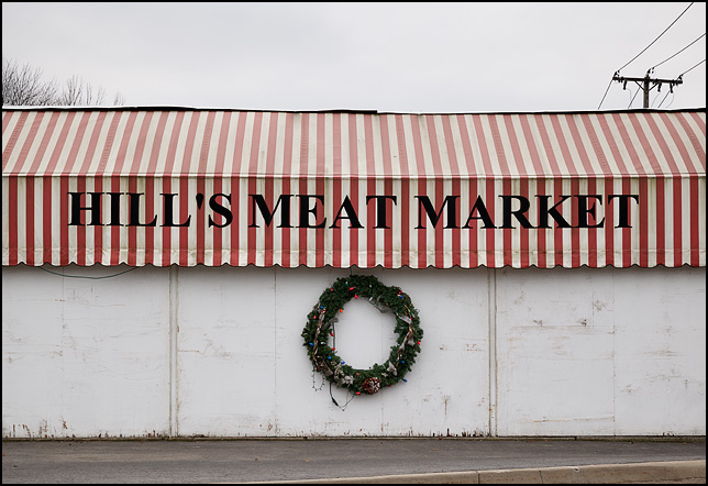 A Christmas wreath hangs on the front of Hills Meat Market, under the white and red striped awning, on Lower Huntington Road in the Waynedale are of Fort Wayne, Indiana.