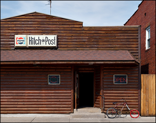 An old bicycle with a wooden front wheel leans against the front of the Hitch-In-Post tavern on High Street in Fort Wayne, Indiana.