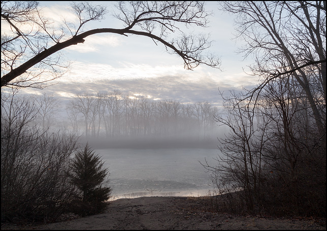Fog at sunrise hangs over the pond at Hodell Acres, the WMCA summer camp on Elmhurst Drive in Fort Wayne, Indiana. The surface of the pond is covered in a thin layer of ice. A view through the trees that surround the deep depression where the pond, a former quarry, is located.