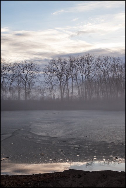 The sun rises on a foggy morning over the pond at Hodell Acres, the WMCA summer camp on Elmhurst Drive in Fort Wayne, Indiana. The surface of the pond is covered in a thin layer of ice.