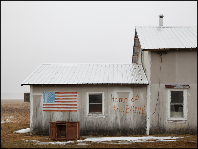 A building with an American flag and the phrase Home Of The Brave spray-painted on it.