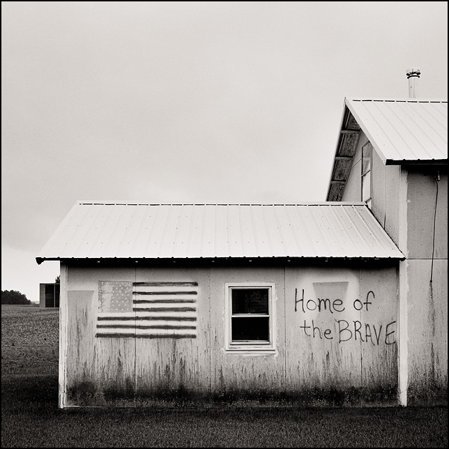 "A spray painted American flag and ""The home of the brave"" on an old barn on 1000N in rural Wells County, Indiana."