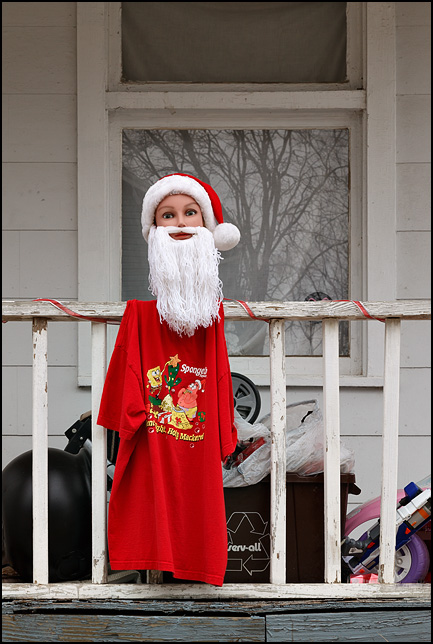 A homemade Santa Claus made from a large female doll's head, a red t-shirt, Santa hat, and a beard made from white yarn hangs on the porch rail of an old house on High Street in Fort Wayne, Indiana. The porch behind Santa is filled with trash and old toys.