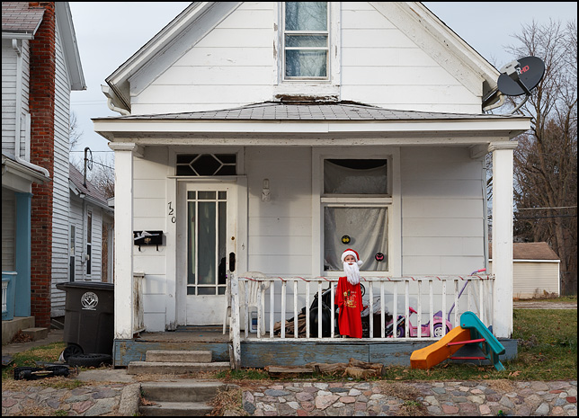 An old white house with a homemade Santa Claus made from a female mannequin head, a red t-shirt, Santa hat, and a beard made from white yarn displayed on the porch.