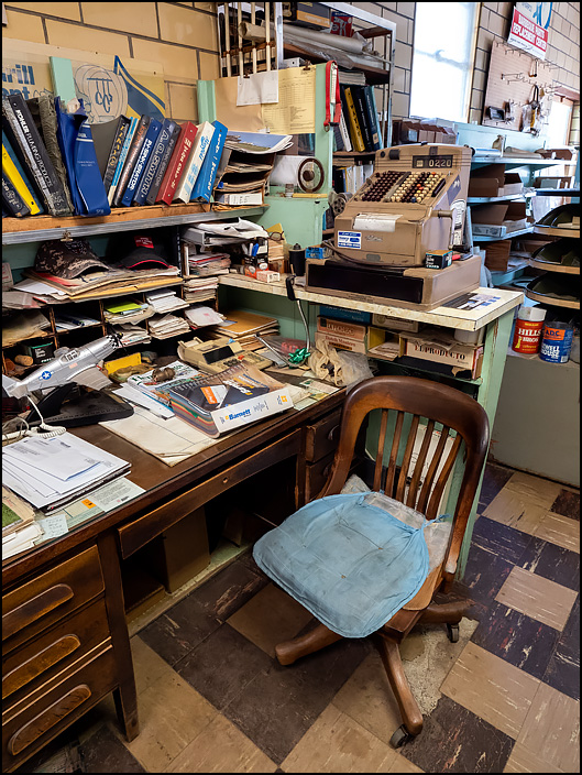 The desk and old wooden office chair used by the late Homer Hoke at Waynedale Plumbing Supply on Lower Huntington Road in Fort Wayne, Indiana. The desk is cluttered with old paperwork and plumbing supply catalogs.
