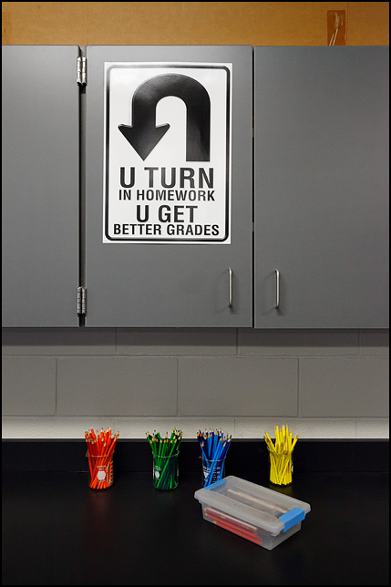 A sign in a middle school science classroom encouraging kids to do their homework. U Turn In Your Homework U Get Better Grades. Glass chemistry beakers full of colored pencils sit on the counter under the sign.