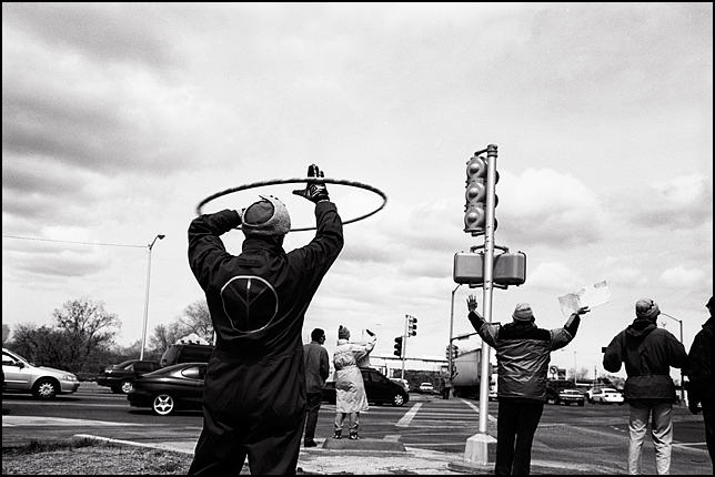 An antiwar activist hula-hoops during the weekly antiwar protest at the corner of Saint Francis Drive and Cerrillos road in Santa Fe. He is protesting the Iraq War and wearing a jumpsuit with a large Peace Sign on the back.