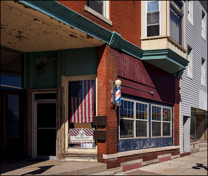 An American flag hangs in the window next to the entrance to Hoosier Barber Shop on Randolph Street in the small town of Garrett, Indiana.