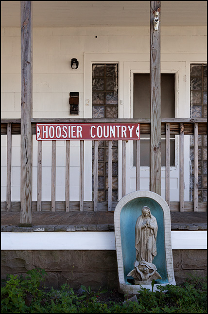 An old house with statue of the Virgin Mary in front of the porch and a sign on the rail that says, Hoosier Country. Located on Williams Street on the south side of Fort Wayne, Indiana.