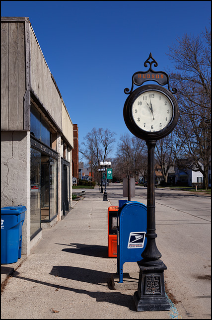 An old-fashioned street clock stands on the sidewalk in front of the post office on Main Street in the small town of Hudson, Indiana. The name of the town is painted above the clock face.