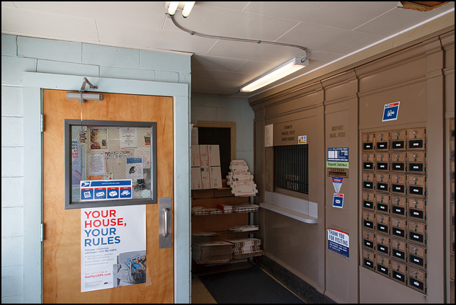 PO boxes line the wall next to the service window inside the cramped lobby of the post office in the small town of Hudson, Indiana.