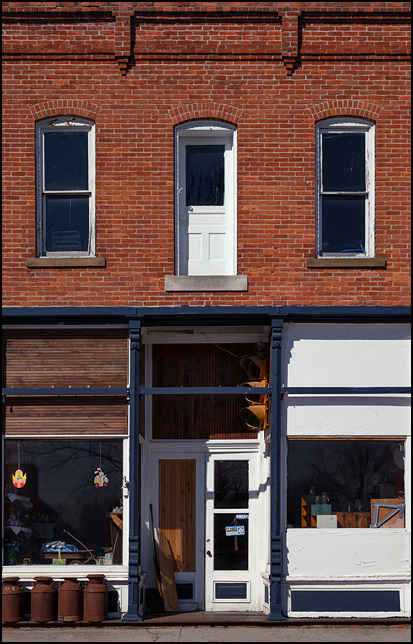 A Main Street brick storefront with a traffic light hanging over the entrance in the small town of Hudson, Indiana. The door on the second floor of the building opens to a long drop to the sidewalk below.