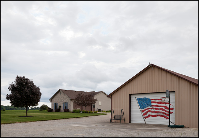 An American flag painted on the door of a garage next to a new house on County Road 400N in rural Huntington County, Indiana. A basketball hoop and a porch swing stand on the driveway in front of the garage.