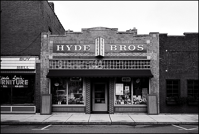 The front of Hyde Brothers Book Store on Wells Street in Fort Wayne, Indiana. The shop is in an old brick storefront whose windows are full of old books.