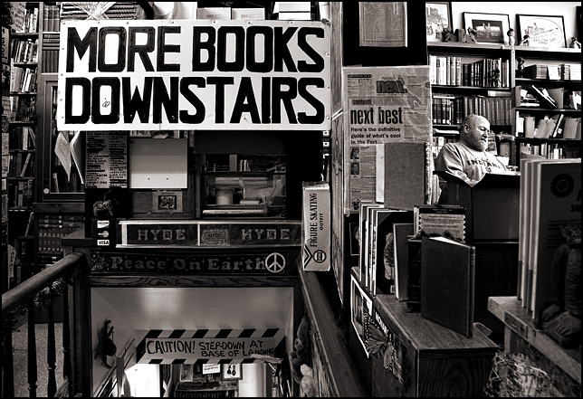 A sign above the basement stairs at Hyde Brothers says that there are more books downstairs. Owner Sam Hyde can be seen behind the counter and a Christmas sign says Peace On Earth.